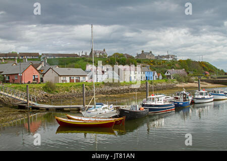 Fishing boats in harbour with row of colourful houses nearby at foot of hill at village of Helmsdale, Scotland - Stock Photo