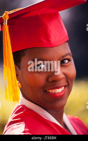 An African American graduate in her red cap and gown with a gold tassel. - Stock Photo
