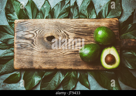 food background with fresh avocado, avocado tree leaves and wooden cutting board. Harvest concept, Guacamole ingredients. - Stock Photo