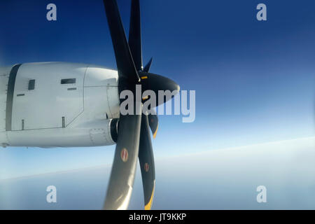 Outside view from window seat of small airplane propeller engine attached to the wings with its black blades rotating - Stock Photo