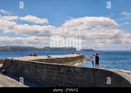 1 July 2017: Lyme Regis, Dorset, England, UK - Visitors strolling on The Cobb on a beautiful sunny summer day. - Stock Photo