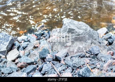 Colorful rocks on Saint Laurent or Lawrence river in Quebec, Canada during summer with brown water - Stock Photo
