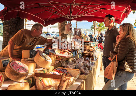 Customers being served at a stall of local meat and cheese in the market, Port of Ajaccio, Island of Corsica, France - Stock Photo