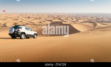 Off road vehicle on sand dunes near Dubai in the United Arab Emirates, Middle East - Stock Photo