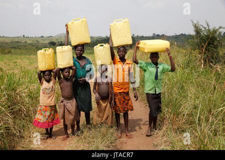 Ugandan children fetching water, Masindi, Uganda, Africa - Stock Photo