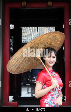 Woman wearing Vietnamese tradition dress called Ao Dai, Taoist temple, Phuoc An Hoi Quan Pagoda, Ho Chi Minh City, - Stock Photo