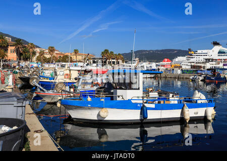 Old Port with fishing boats, cruise ship and ferries, view to distant mountains, Ajaccio, Island of Corsica, France - Stock Photo