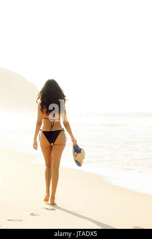 Young Brazilian (Latin American) (Latina) woman in golden dawn light on the beach in a bikini, Rio de Janeiro, Brazil - Stock Photo