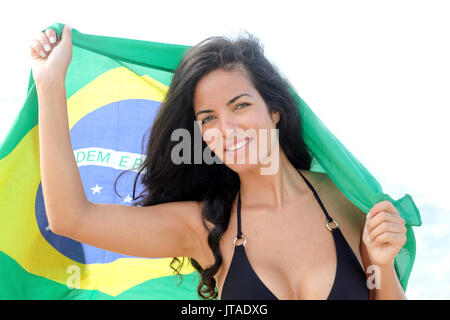 Young Brazilian woman, 20 to 29 years old, holding the Brazilian flag on a beach in Rio de Janeiro, Brazil - Stock Photo