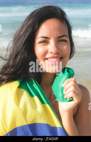Young Brazilian woman, 20 to 29 years old, wrapped in the Brazilian flag on a beach in Rio de Janeiro, Brazil - Stock Photo