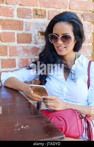 Young Brazilian (Latin American) (Latina) woman, 20 to 29 years old using her mobile phone in a cafe, Rio de Janeiro, - Stock Photo