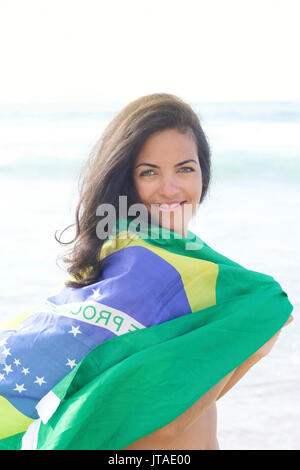 Young Brazilian woman 20 to 29 years old with a Brazilian flag beach wrap on a beach, Rio de Janeiro, Brazil - Stock Photo