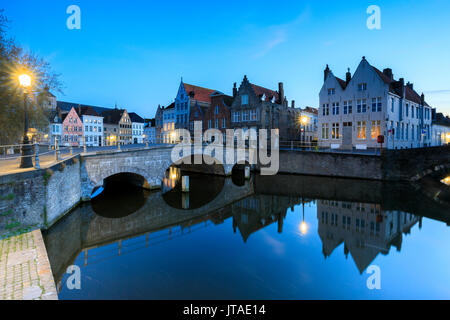 Dusk lights on the historic buildings of the city centre reflected in the typical canals, Bruges, West Flanders, - Stock Photo