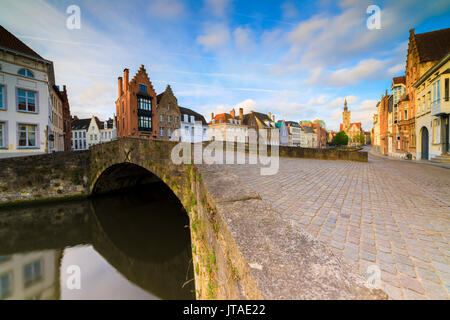 Pink clouds at dawn on the typical buildings and quay along the typical canal, Bruges, West Flanders, Belgium, Europe - Stock Photo