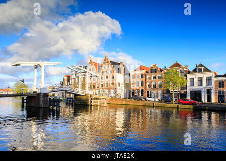Blue sky and clouds on typical houses reflected in the canal of the River Spaarne, Haarlem, North Holland, The Netherlands - Stock Photo