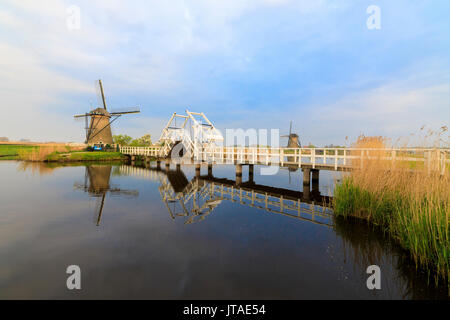 Traditional windmills and bridge on the canal framed by sunrise, Kinderdijk, UNESCO, Molenwaard, South Holland, - Stock Photo