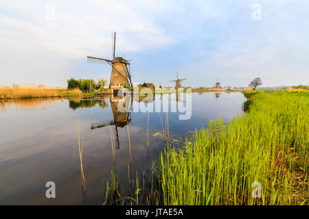 Dawn on windmills reflected in the canal surrounded by green meadows, Kinderdijk, UNESCO, Molenwaard, South Holland, - Stock Photo