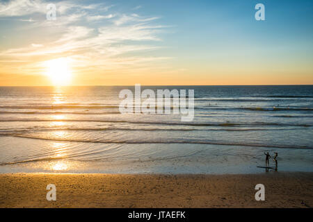 Couple in backlight walking at sunset, Del Mar, California, United States of America, North America - Stock Photo