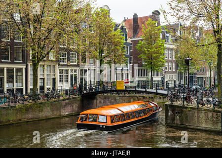Canal boat passing under a bridge on Brouwersgracht, Amsterdam, Netherlands, Europe - Stock Photo
