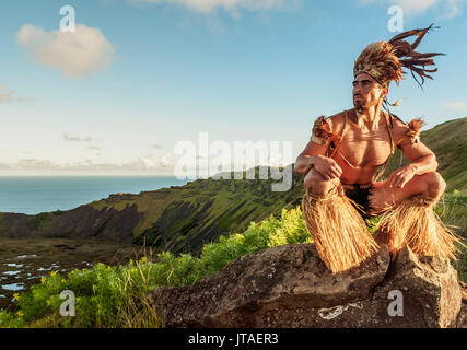 Native Rapa Nui man in tradititional costume on the rim of the Rano Kau Volcano, UNESCO, Easter Island, Chile - Stock Photo