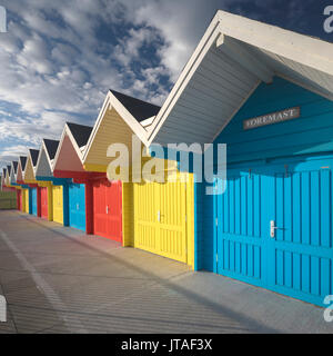 Row of colourful beach huts lit by early morning summer sunlight on the seafront at Whitby, North Yorkshire, England, - Stock Photo