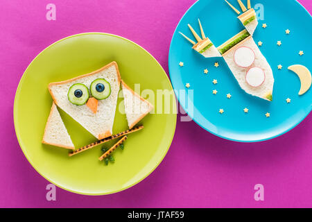 Funny colorful breakfast for child in shape of owl and rocket isolated on pink - Stock Photo