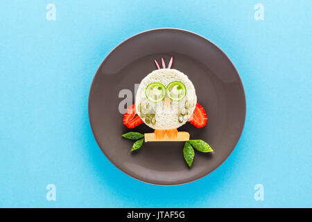 Funny colorful breakfast for child in shape of owl isolated on blue - Stock Photo