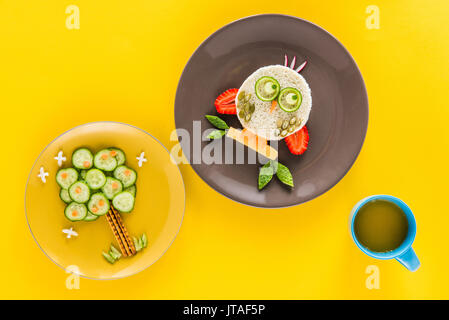 Funny colorful breakfast for child in shape of owl and tree isolated on yellow - Stock Photo