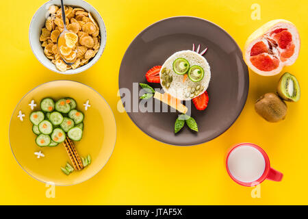 Funny colorful breakfast for child in shape of owl and tree with cornflakes, fruits and milk isolated on yellow - Stock Photo