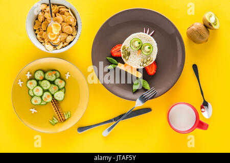 Funny colorful breakfast for child in shape of owl and tree with cornflakes, kiwi and milk isolated on yellow - Stock Photo