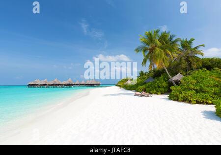 View along tropical beach towards over-water villas, Coco Palm Resort, Dhuni Kolhu, Baa Atoll, Republic of Maldives - Stock Photo