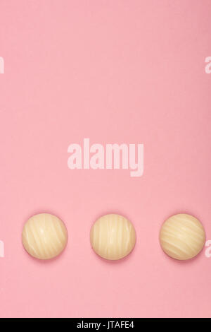 Top view of three white chocolate candies isolated on pink background - Stock Photo