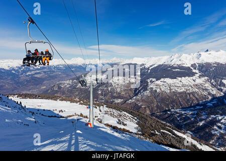 Skiers on a chair lift, Veysonnaz (Verbier), 4 Vallees, Valais, Swiss Alps, Switzerland, Europe - Stock Photo