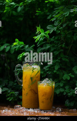 Citrus lemonade with herbs on a wooden background. Orange lemonade with tarragon - Stock Photo