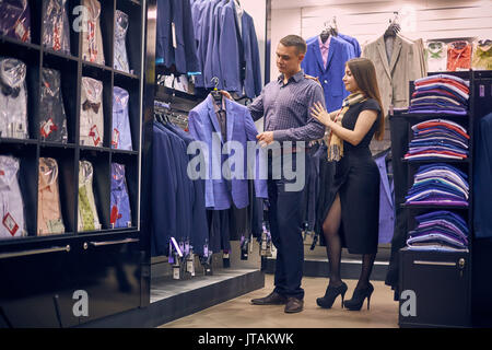 a9bc563942 Young couple choose a jacket in the store. Loving guy and girl buy clothes  in
