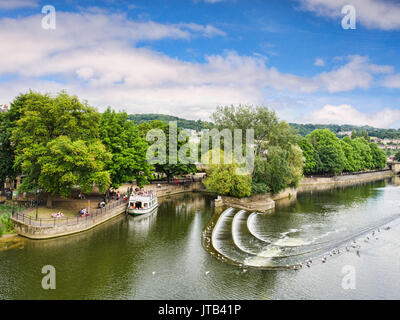 8 July 2017: Bath, Somerset, England, UK - Pulteney Weir, one of the attractions of the city, and a pleasure boat - Stock Photo