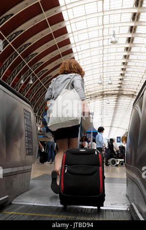 A view of the roof and a young woman with her luggage walking onto the concourse from an escalator at Paddington - Stock Photo