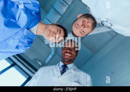 bottom view of multiracial group of doctors standing in circle in clinic - Stock Photo