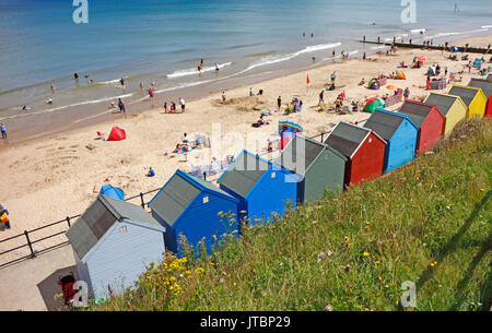 A view of people enjoying the beach with beach huts at the North Norfolk resort of Mundesley-on-Sea, Norfolk, England, - Stock Photo