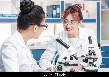 scientists working together with microscopes in chemical lab, scientists team concept - Stock Photo
