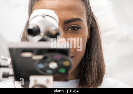 partial view of woman scientist looking through microscope on reagents in laboratory   - Stock Photo