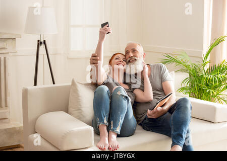 Happy mature couple taking selfie while sitting on sofa at home - Stock Photo