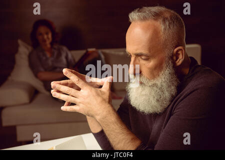 tired grey haired man sitting at table in thoughtful pose - Stock Photo