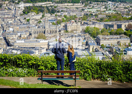 A man and a woman are pictured looking down from Alexandra Park and taking a photograph of a scenic view of the - Stock Photo