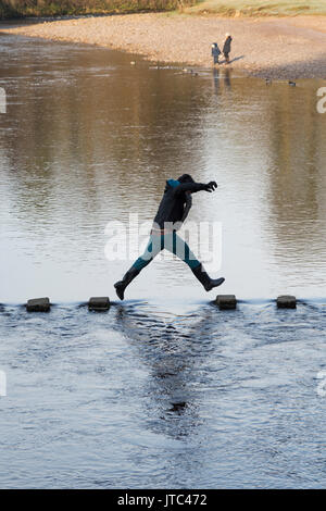 Man jumping across the stepping stones over the River Wharfe at Bolton Abbey in the Yorkshire Dales National Park - Stock Photo