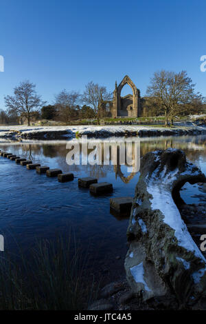 Bolton Abbey, North Yorkshire Dales National Park with stepping stones over the river Wharfe in winter with snow - Stock Photo