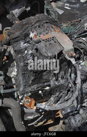 Burned and damaged car battery after fire accident - Stock Photo