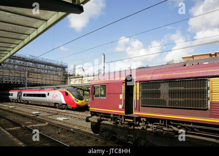 Virgin Trains class 390 Pendolino high speed train and EWS class 66 diesel locomotive at Carlisle station. UK. - Stock Photo