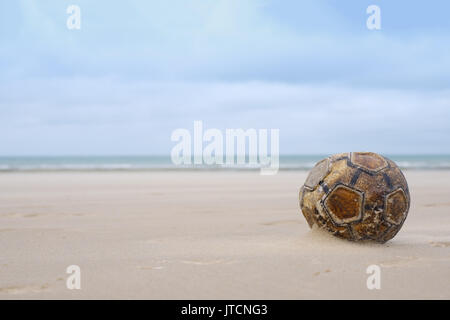 Old leather football soccer ball sits on sand beach - Stock Photo