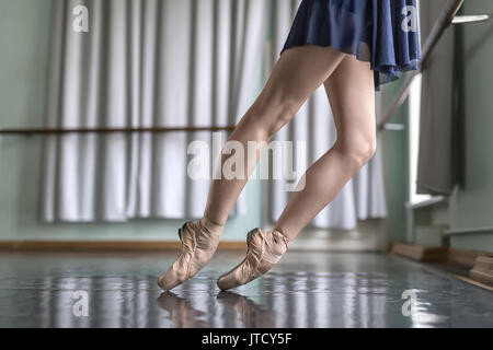 Legs of a ballet dancer in a blue dance wear who stands on pointes next to the ballet barre. She wears beige pointe - Stock Photo